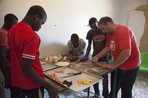 Jorge Reina (right), a Venezuelan bread maker, shows a group of young men how to prepare dough to be baked. A former drug smuggler who met Christ, Reina moved to Senegal a year ago to feed boys, teach them bread-making skills and disciple them.