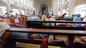 "A child uses a pew as a makeshift bed inside the Redemptorist Church in Tacloban City where residents evacuated ahead of the landfall of Typhoon ""Ruby"""