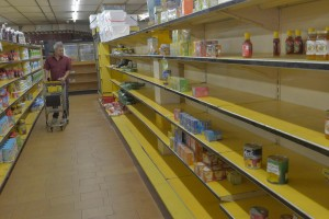 CARACAS, VENEZUELA - JANUARY 13: A shopper walks past nearly empty shelves at a supermarket due to a long term shortage in Caracas, Venezuela on January 13, 2015. Sliding oil prices have sent Venezuela on a downward spiral and sent President Nicolas Maduro on a trip to China to make an urgent appeal for cash. Country's economic woes have triggered severe shortages of some staple product, with government-controlled supermarkets now limiting the amount of certain products customers can purchase. (Photo by Carlos Becerra/Anadolu Agency/Getty Images)