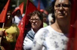 Demonstrators holding flags gather in front of the Portuguese parliament as they participate with hundreds of others in a demonstration