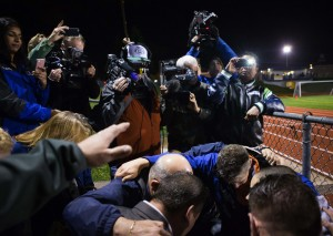Coach Joe Kennedy, in blue, bottom, takes a knee with a few others to do a quick prayer in the stands after the Bremerton Knights beat the Sequim Wolves at Memorial Stadium in Bremerton on Thursday, Oct. 29, 2015. Bremerton assistant football coach Joe Kennedy was placed on administrative leave on Wednesday following his decision to pray on the field after he was told not to by the school district. The Satanic Temple of Seattle announced this week that they planned to be at the game on Thursday after a 12th-grader at Bremerton High School had requested the group perform a satanic invocation.  (Lindsey Wasson / The Seattle Times)