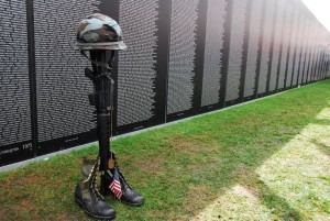 A helmet, rifle, set of dog tags and pair of boots, called a Fallen Soldier Battle Cross, stands in front of the Vietnam Memorial War replica in tribute to those killed in action at the Vietnam Veterans Homecoming Celebration at the Charlotte Motor Speedway March 31. (Photo by Sgt. Katryn Tuton/ 50th Public Affairs Detachment).
