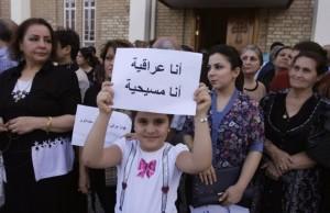 Iraqi girl holds a sign: 'I am Iraqi. I am a Christian.'