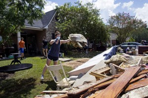 Hannah McLain, 22, a volunteer organized by a local Baton Rouge church, helps throw out waterlogged items from the home of Rhonda Brewer in Baton Rouge, La., Tuesday, Aug. 16, 2016. Around 100 students from LSU and local high schools also helped residents clean up in the area.  At least 40,000 homes were damaged and eight people killed in the historic Louisiana floods, the governor said Tuesday, giving a stark assessment of the widespread disaster. (AP Photo/Max Becherer)