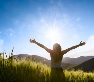 woman silhouette facing the sun with hands outstretched in wheat field