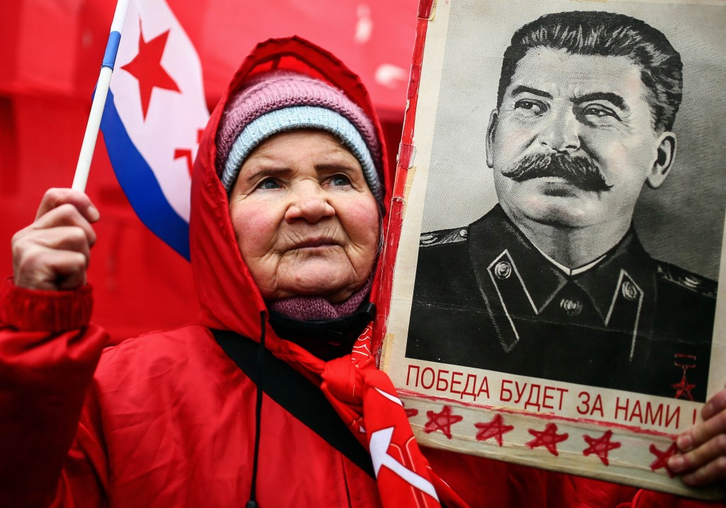 "TOPSHOTS A Russian Communist holds up a portrait of former Soviet dictator Josef Staline during a rally marking ""Defender of the Fatherland Day"" in Moscow on February 23, 2014. AFP PHOTO/ MIKHAIL LISTOPADOV"