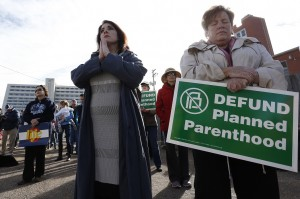 Participants in an anti-abortion rally hold signs and pray as they listen to a member of Christian clergy read from the Bible, in front of Planned Parenthood of the Rocky Mountains, in Denver, Saturday, Feb. 11, 2017. Anti-abortion activists emboldened by the new administration of President Donald Trump staged rallies around the country Saturday calling for the federal government to cut off payments to Planned Parenthood. (AP Photo/Brennan Linsley)