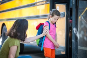One of a series of First Day of School images, showing a young girl going through the emotions of getting on the bus for the first time.