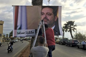 "Workers hang a poster of outgoing Prime Minister Saad Hariri with Arabic words that read:""We are all Saad,"" at a seaside street in Beirut, Lebanon, Thursday, Nov. 9, 2017. Hezbollah has called on Saudi Arabia to stay out of Lebanese affairs, saying the resignation of Prime Minister Saad Hariri, announced from Riyadh over the weekend, ""has raised many questions."" (AP Photo/Hussein Malla)"