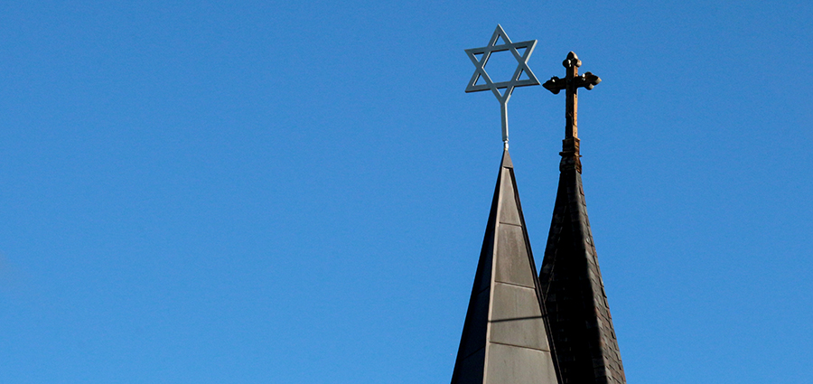 Perspective of church and synagogue spires atopped with a cross and Star of David.  The two spires appear to be overlapping in a clear sky.