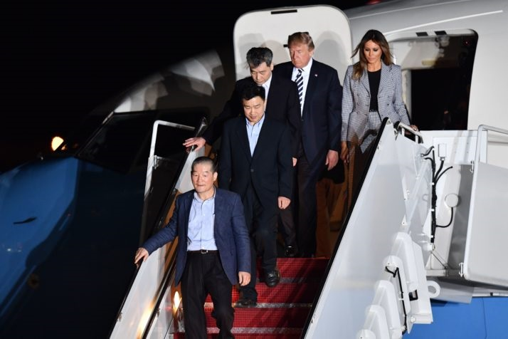 US President Donald Trump (2nd R) and his wife Melania Trump (R) walk down the stairs with US detainees Tony Kim (2nd L), Kim Dong-chul (bottom L) and Kim Hak-song (C) upon their return after they were freed by North Korea, at Joint Base Andrews in Maryland on May 10, 2018. - US President Donald Trump greeted the three US citizens released by North Korea at the air base near Washington early on May 10, underscoring a much needed diplomatic win and a stepping stone to a historic summit with Kim Jong Un. (Photo by Nicholas Kamm / AFP)        (Photo credit should read NICHOLAS KAMM/AFP/Getty Images)